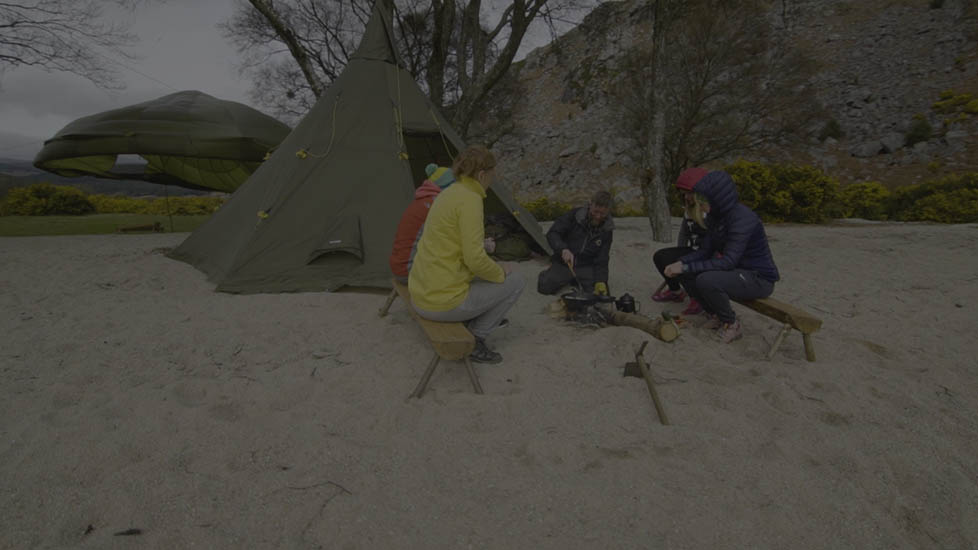 Bear Grylls Survival Academy participants learning how to light fires on the beach.