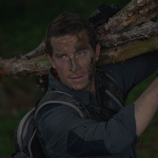 Bear Grylls holding a log during his survival academy.