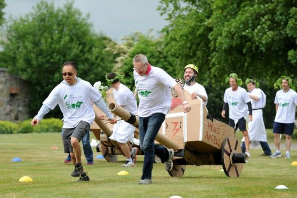 Delegates working together to pull their chariot they built, during the final race of Flat Out Chariots, a corporate game.