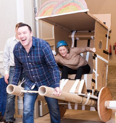 Team smiling and laughing while racing their rickshaw during the finale of the Flat Out corporate team building game.
