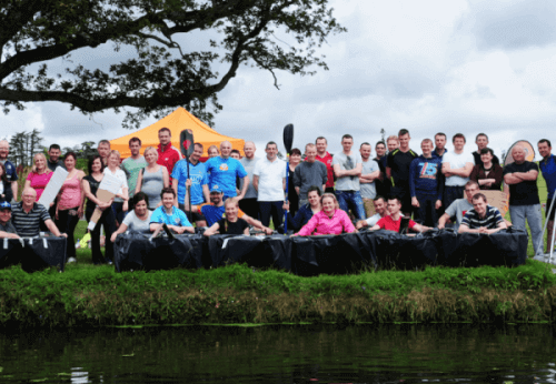 Delegates standing beside the cardboard boats they built and designed during Flat Out Afloat, a corporate team-building game.