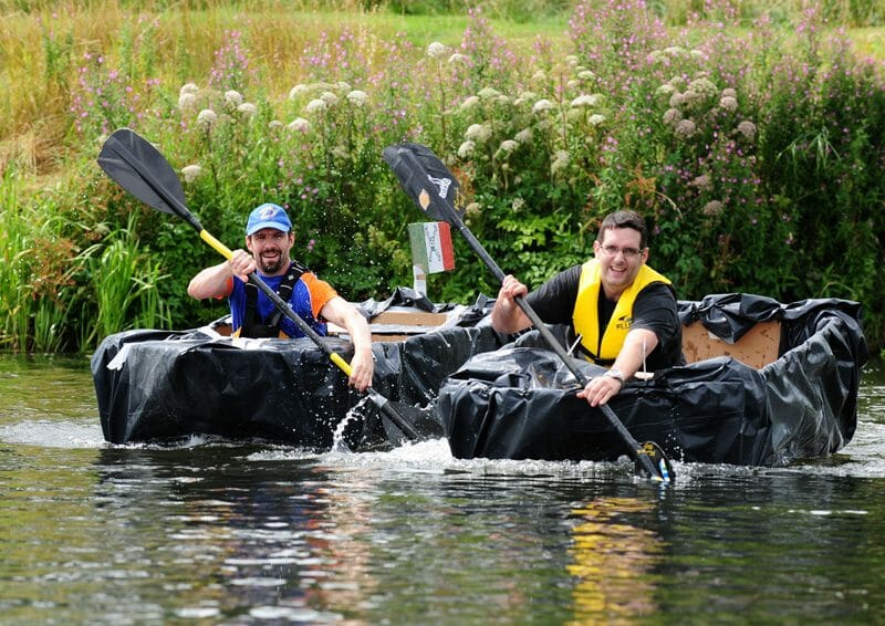 Delegates rowing down the river in a cardboard boat he built during his team-building activity with Orangeworks.