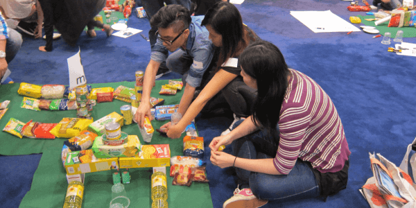 Teams building a golf course out of non-perishable foods during Hole in One, a team building charity focused activity.