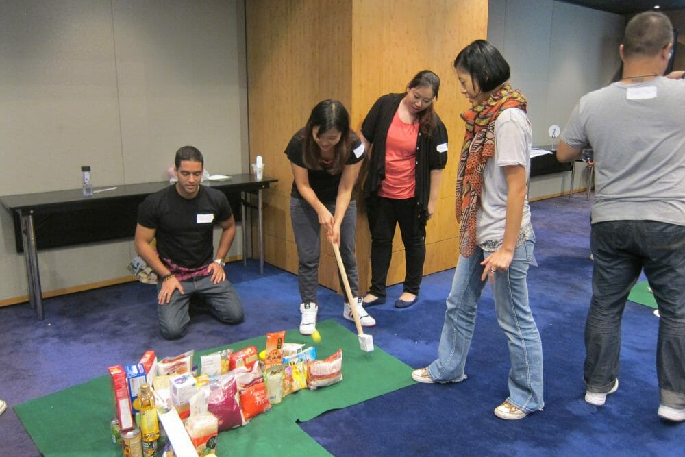 Delegates playing golf together on their sustainable pitch and putt course they built during their team building activity.
