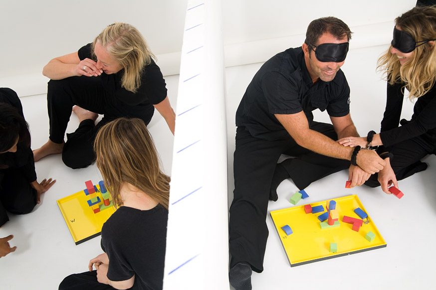 Blindfolded delegates helping one another complete construction challenges during Orangeworks team game 'Breakthrough'.