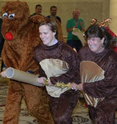 3 employees dressed as reindeers pulling Santa's sleigh during the christmas themed Team Building Game by Orangeworks.