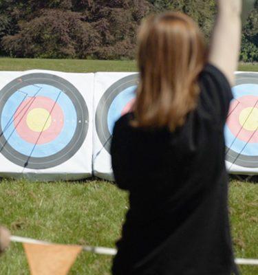 Delegate cheerfully raising hand during their archery team activity with Orangeworks