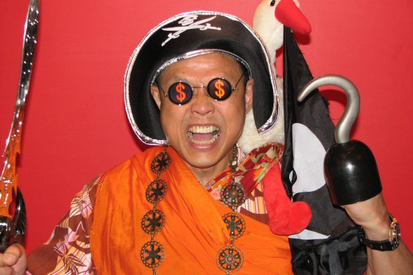 A man posing as a pirate for the team engagement event by Orangeworks. He has a hat and parrot on his shoulder and is holding a hook and a sword.