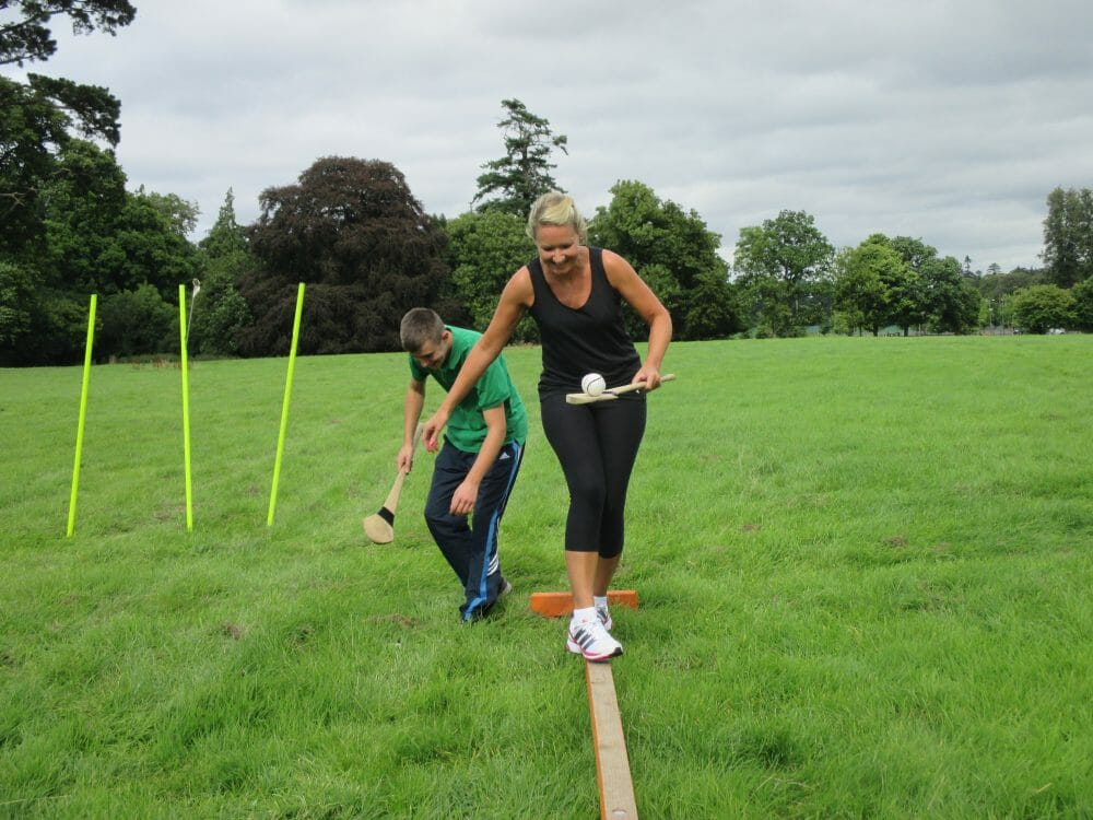 Two delegates trying to balance on a beam with a hurl and sliotar during their Hurling workshop with Orangeworks.