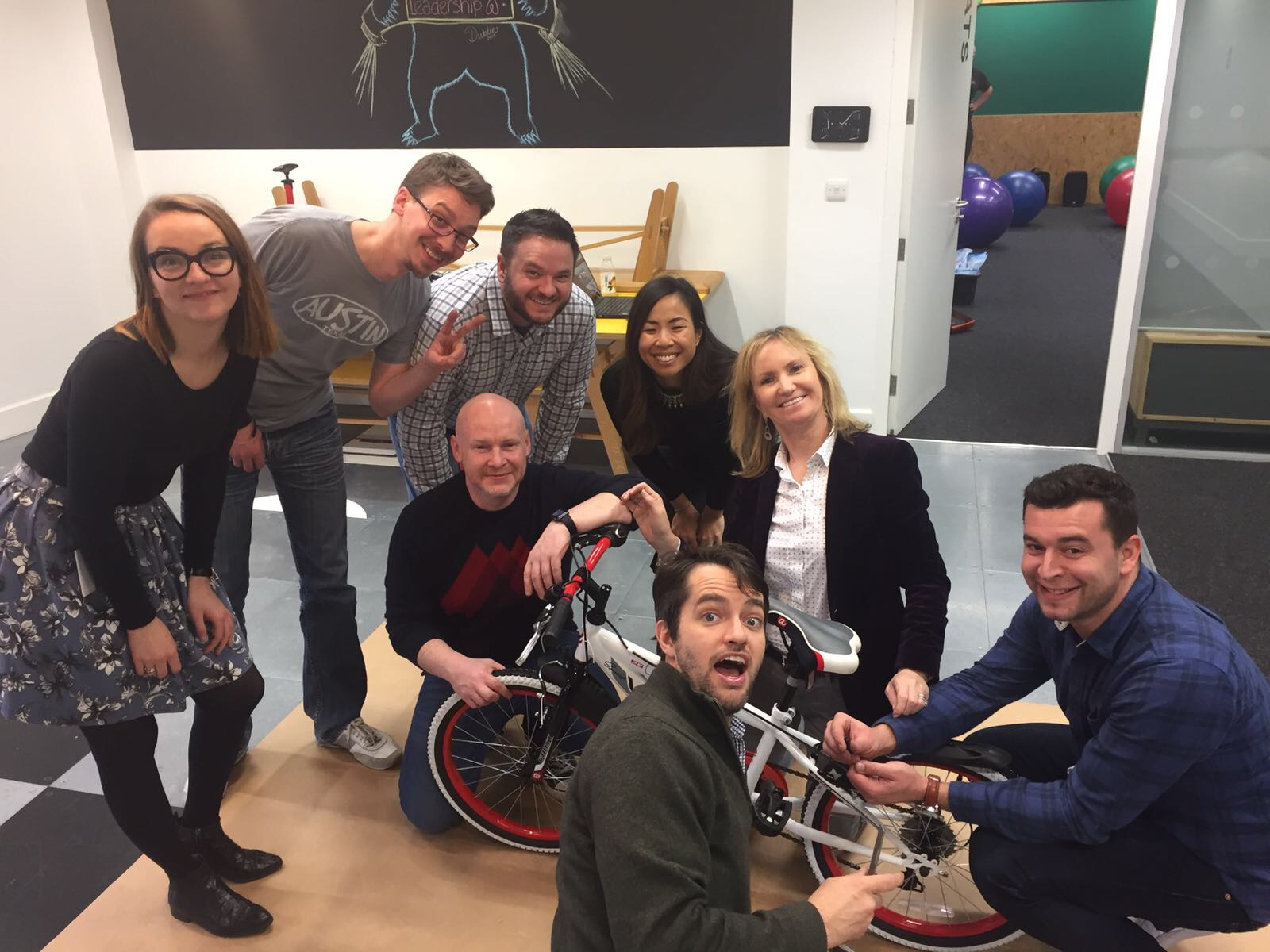 Charity Bike Build- Corporate Social Team smiling with their newly built bike for charity during Orangeworks team building activity Charity Bike Build.
