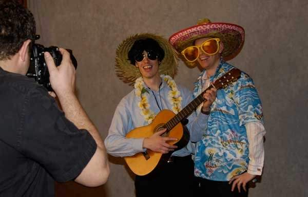 Two delegates of the fun team bonding activity, In The Picture, posing for a photo wearing big hats and sunglasses and holding a guitar.