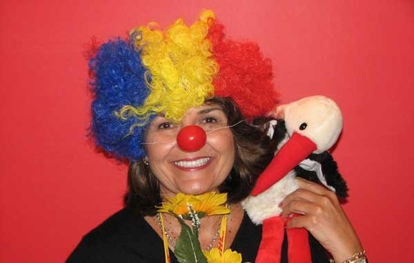 A participant dressed up as a clown with a funny wig and nose on for the team-building exercise In The Picture by Orangeworks.