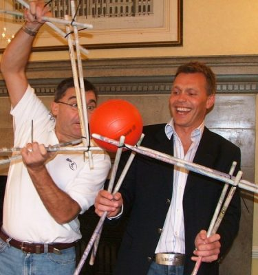 Delegates balancing a ball using bamboo sticks during Mexican Railway, a team building game with Orangeworks.