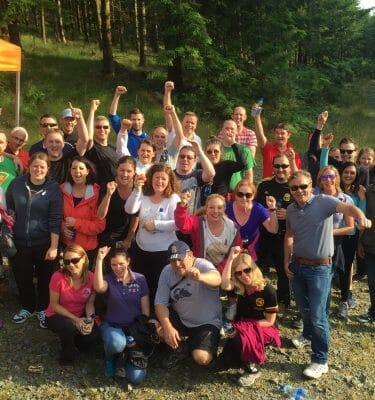 Happy group of delegates smiling after completing Xtreme Forest Adventure.