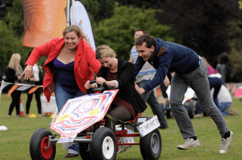 Team members pushing their colleague on a go-kart as they race in the final of Thunder Races, an outdoor team-building event.