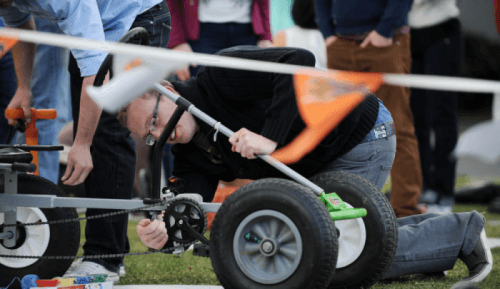 A team member bending down fixing the chain of a go-kart as he prepares for the final race of Thunder Races by Orangeworks.