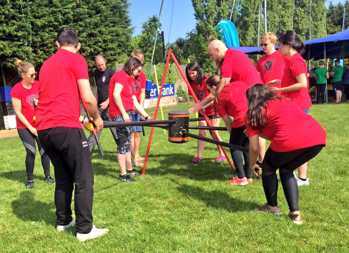 Delegates wearing red shirts working together to figure out the box challenge, as part of their corporate sports day activity