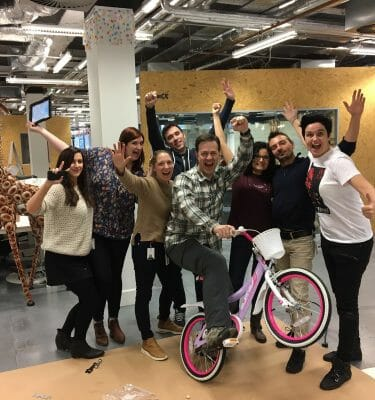 Team smiling with their newly built bike for charity during Orangeworks team building activity Charity Bike Build.