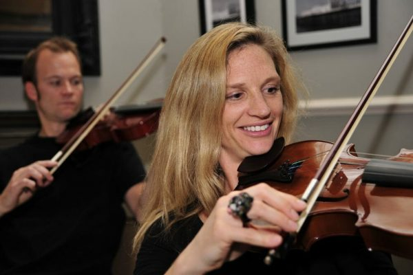 A woman holding her violin practising the cords for the final performance of Orchestrate. A man behind her doing the same.