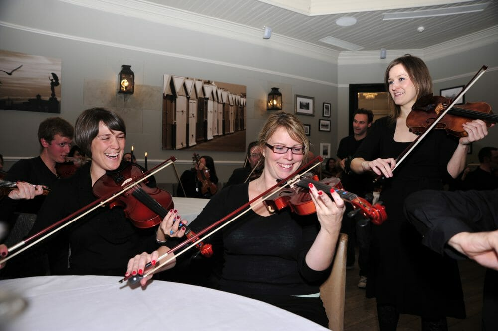 Delegates learning how to play the violin during their music-themed team building activity, Crescendo, with Orangeworks.