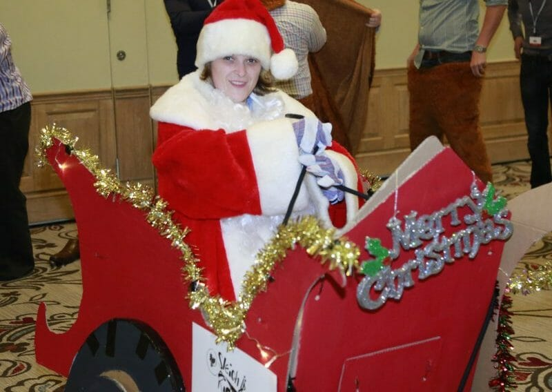 A delegate dressed as Santa in a cardboard sleigh that she and her teammates built during a christmas themed team game.