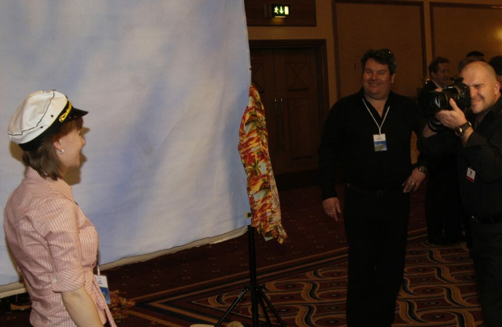 A delegate of the Orangeworks corporate icebreaker event, In The Picture, wearing a sailor hat and smiling for a photo.