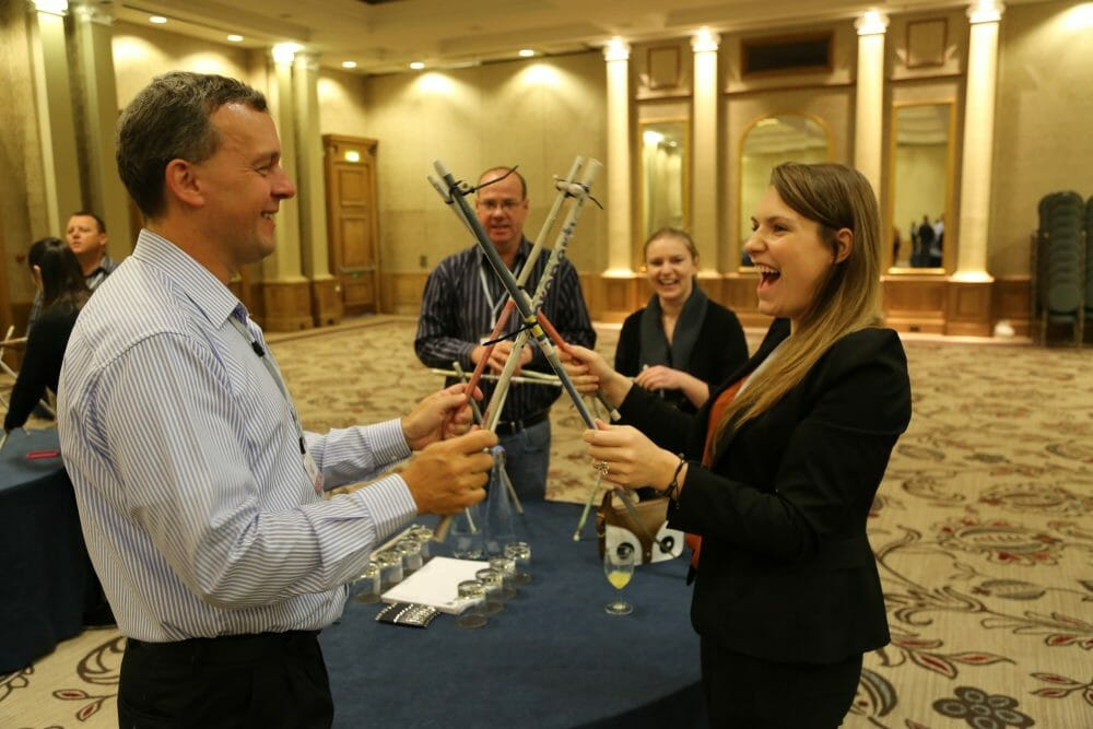 Smiling delegates working together to build their first part of Mexican Railway, an Orangeworks team bonding challenge.