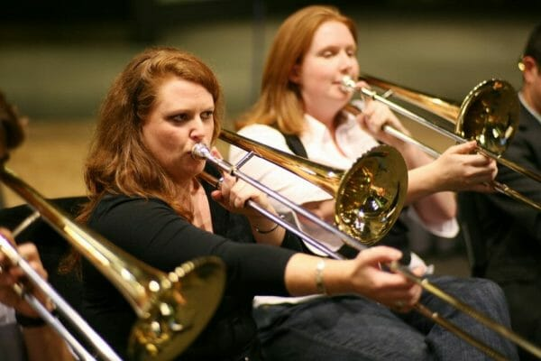 2 women playing the trumpets during Orchestrate, a musical team-building challenge by Orangeworks.
