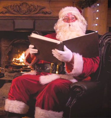 Santa Claus sitting by the fire with a book in his hands