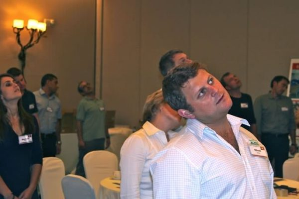 A man moving his head to the side along with other delegates conducting relaxing exercises during We Can Do, a wellbeing session for employees.