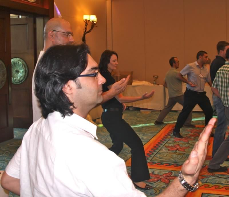 Participants of the employee wellness program We Can Do by Orangeworks standing with their hands in the air while practising their karate moves.