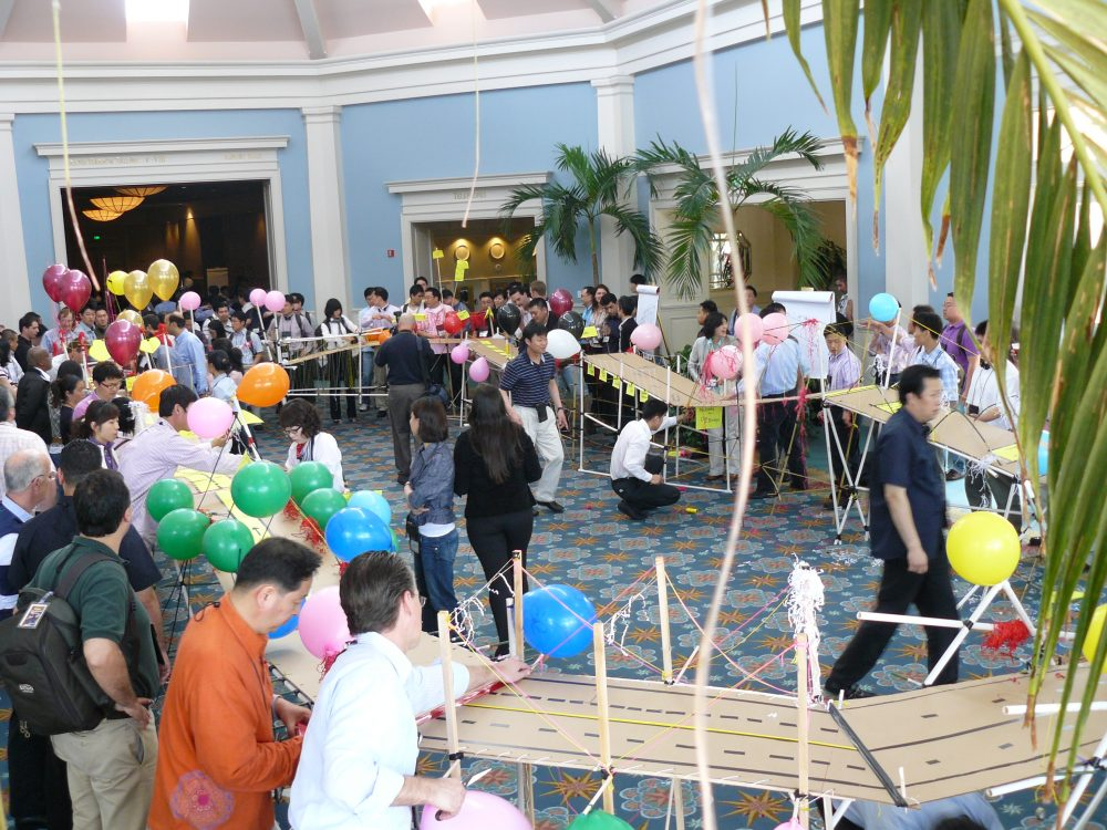 Teams stand around their completed bridge they have constructed, during a fun team building experience with Orangeworks.