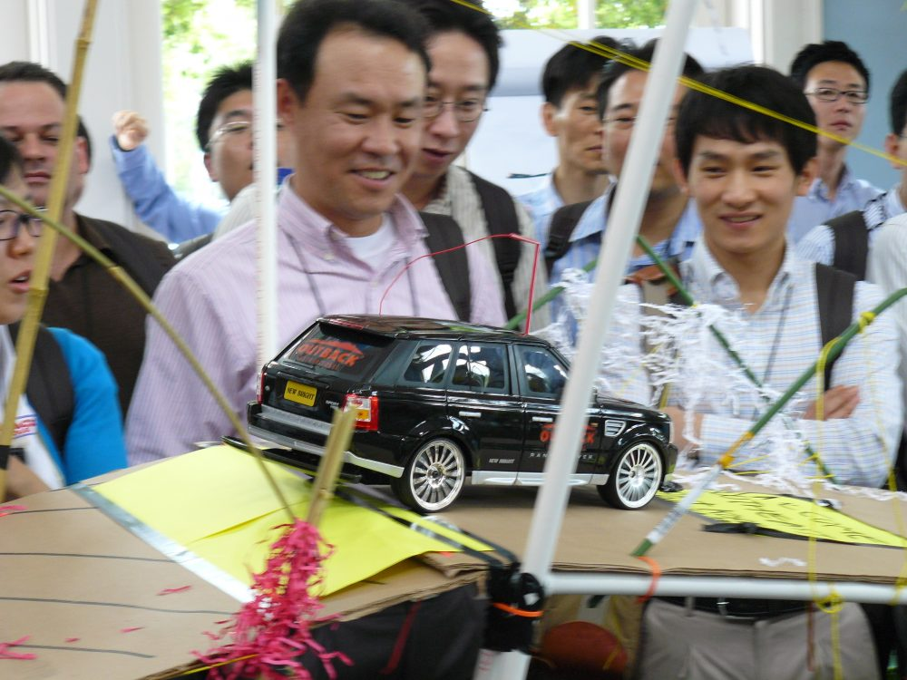Delegates smiling as they drive the toy car across the cardboard bridge they created during Bridging the Divide.