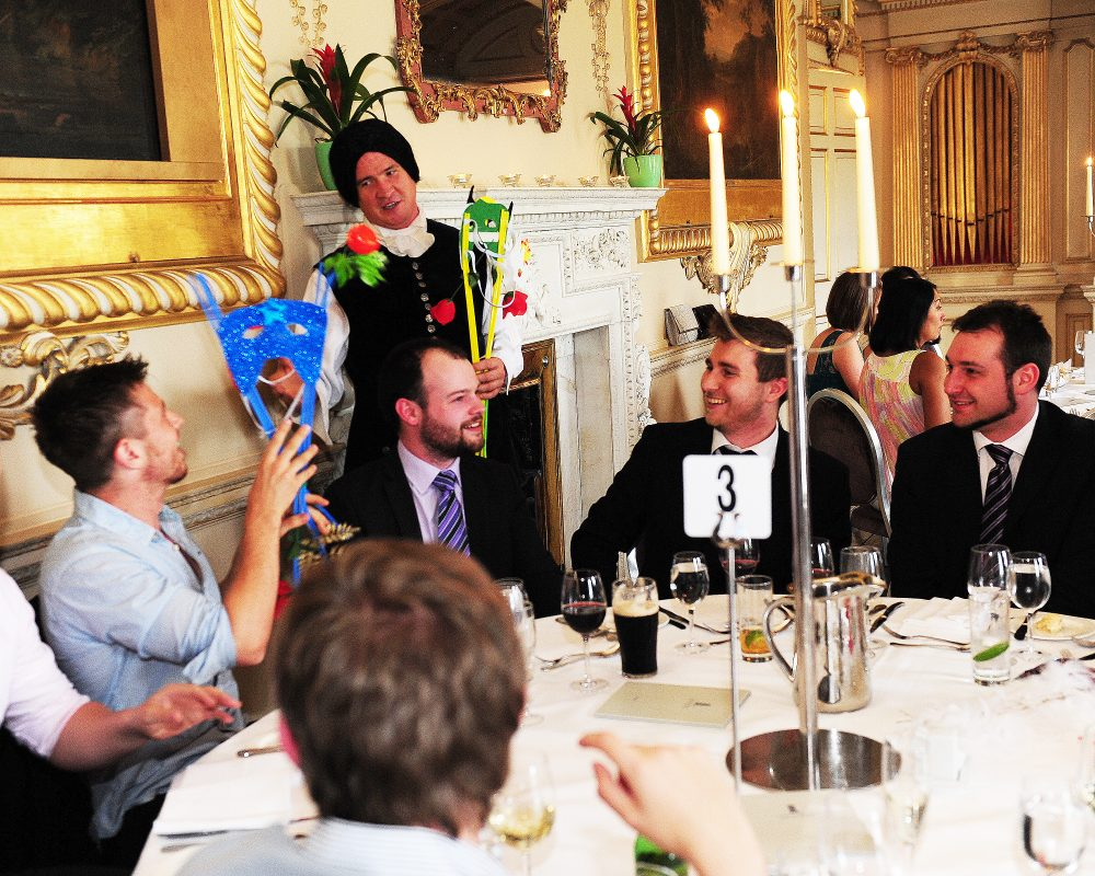 Delegates looking at the different masks used for their murder mystery-themed corporate dinner hosted by Orangeworks.