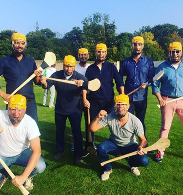 Delegates smiling with their hurls, wearing yellow helmets during a Hurling Workshop as part of their corporate sports day.