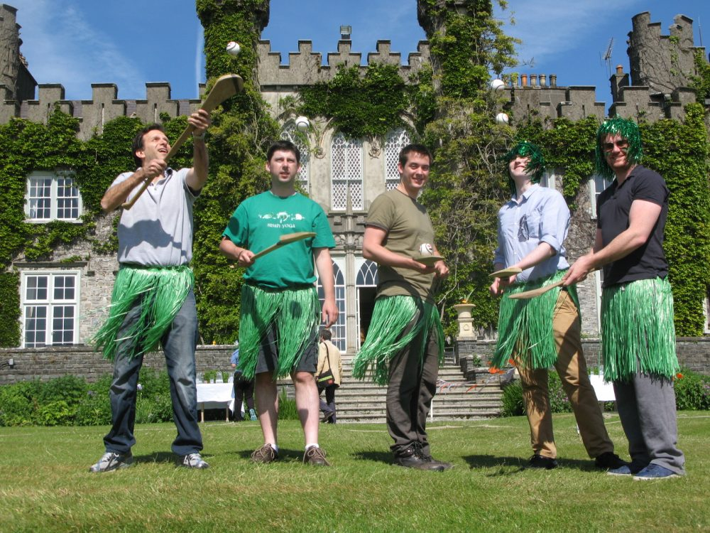 Delegates wearing grass hula skirts holding hurls and sliotars as part of their team building day with Orangeworks.