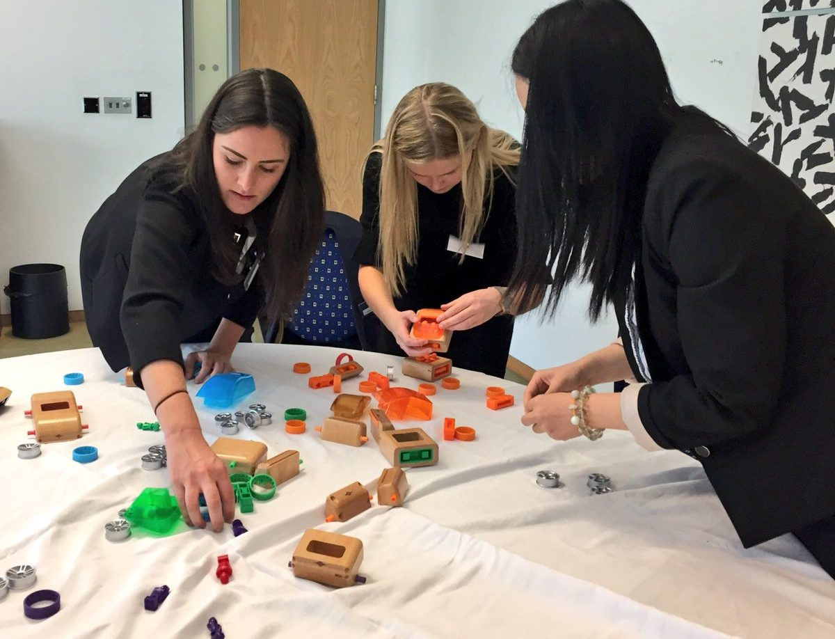 Delegates work together to build model cars during Orangeworks team building game called need for speed.