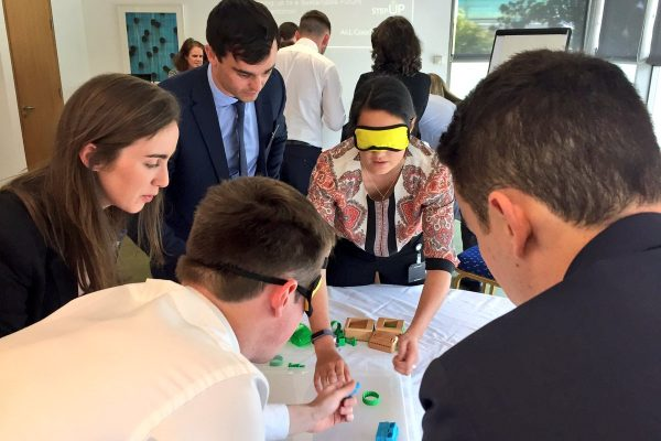 Blindfolded delegates putting together their cars during Need 4 Speed, a charity themed corporate team building game.
