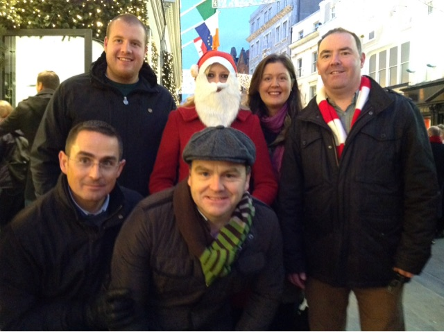 Teams standing around a person posing as Santa doing the photo challenge of Go Team Hunt for Santa with Orangeworks.