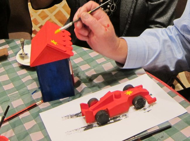 Participant painting a toy house and car during a charitable team bonding activity called Toy Factory, hosted by Orangeworks.