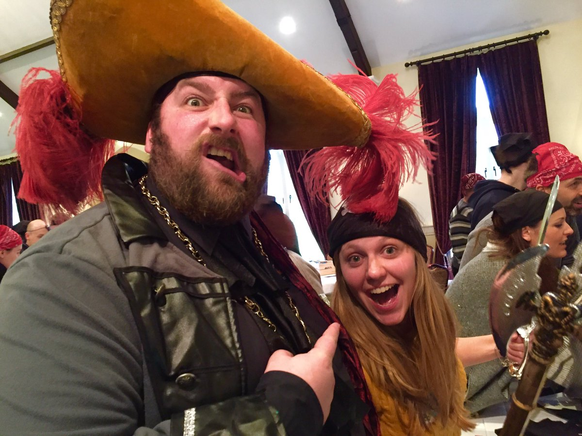 Oddie and a delegate of Orangeworks team bonding game, Trade Winds, wearing pirate hats and smiling.
