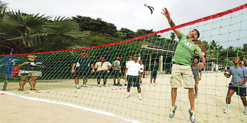 Delegate jumping in the air to hit the target over the net.
