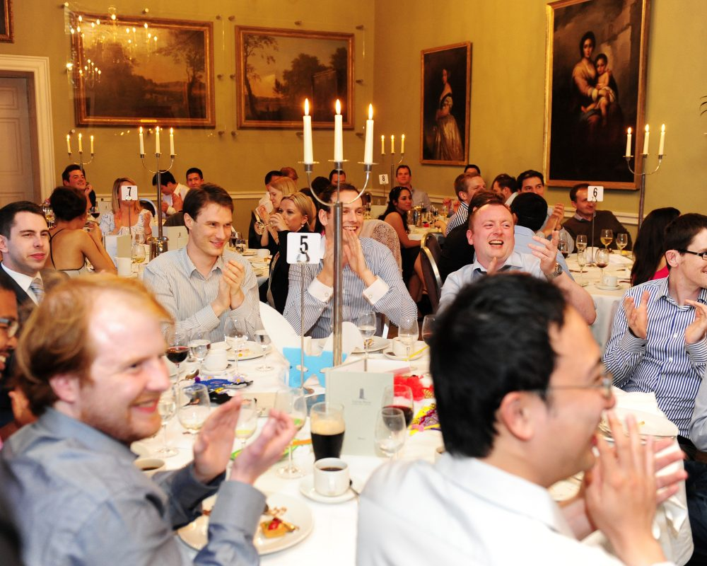 Delegates sitting around a table clapping during the final moments of their 1916 Murder Mystery dinner with Orangeworks.