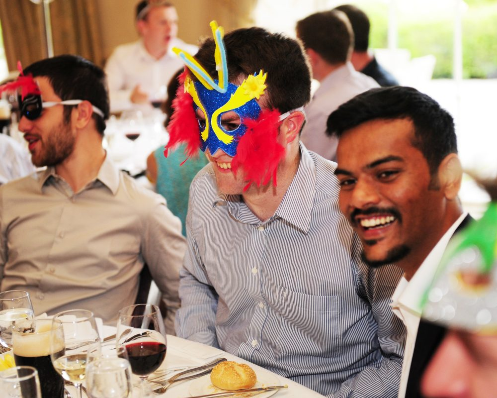 Delegates wearing masquerade masks, sitting at the dinner table playing their Murder Mystery corporate evening Interaction.