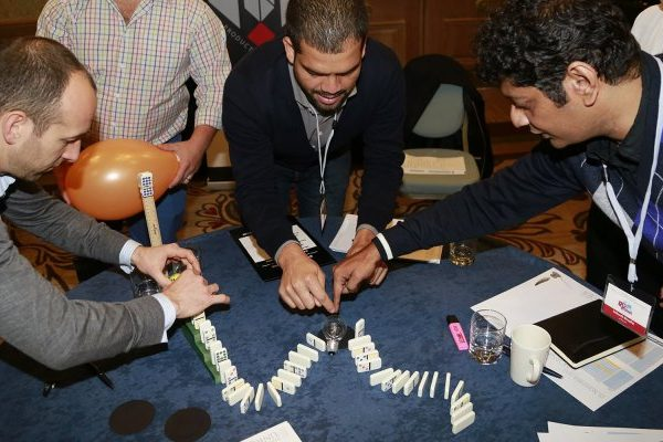 Delegates working together to line up their dominos during a team-building activity with Orangeworks called Domino Effect.