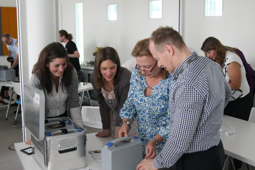 Delegates working together to open the first silver case of the escape room style corporate team bonding game, Beat the Box.