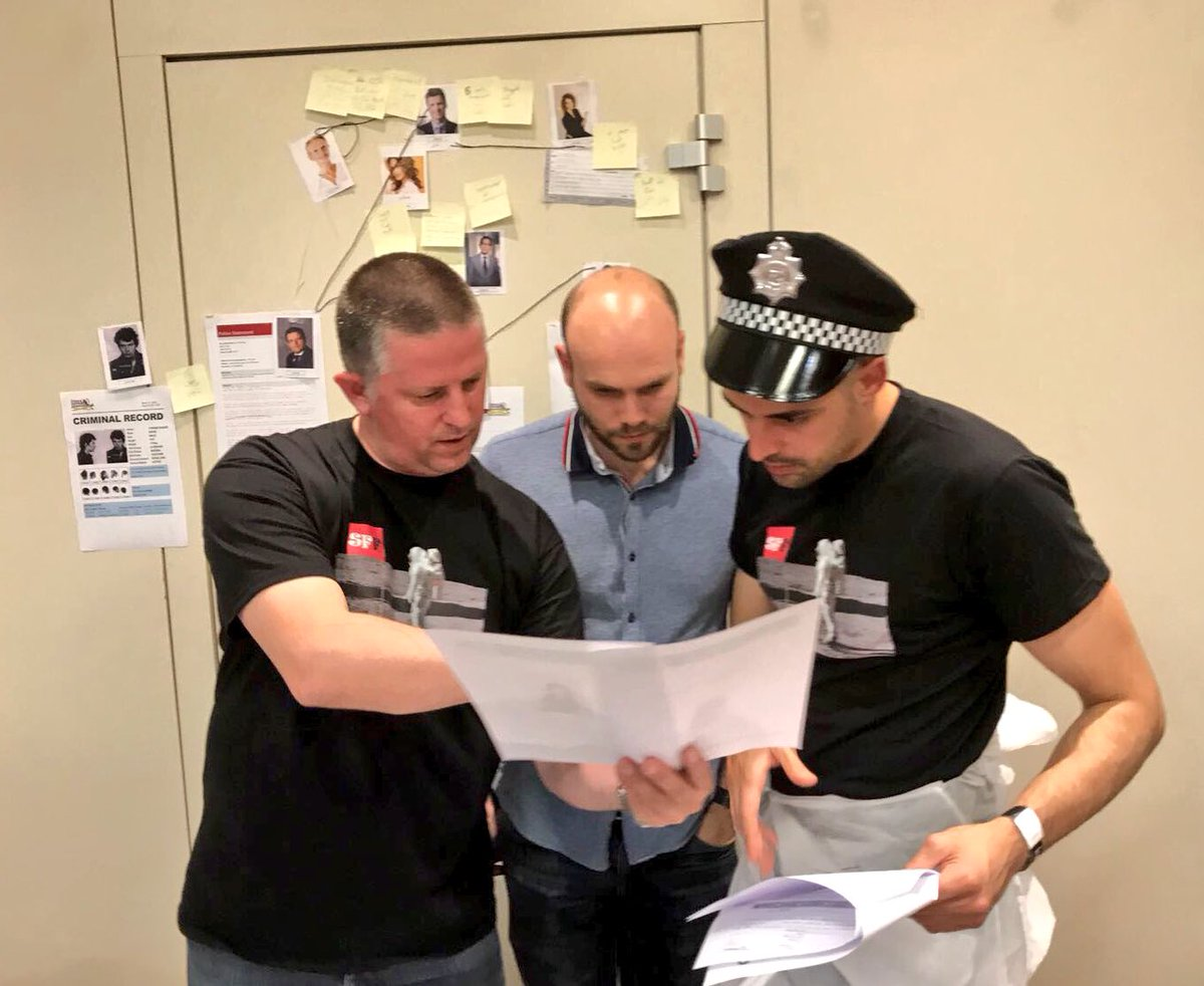 Delegates working together looking for crime clues during their CSI themed business game with Orangeworks.