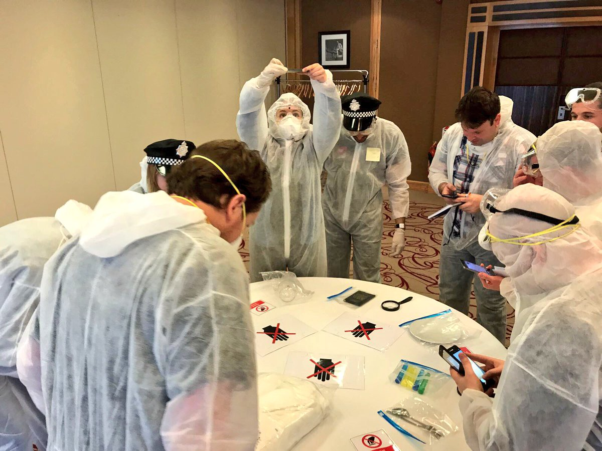 Delegates wearing white overalls looking for crime clues during their CSI themed business game with Orangeworks.