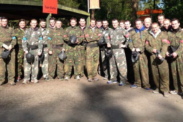 Team standing together wearing army overalls, as they are about to commence their team building activity with Orangeworks.