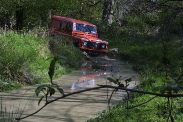 Orangeworks landrover defender driving through a muddy off-road track at our Carton House off road driving track.